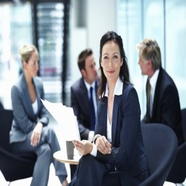 Portrait of business woman smiling with executives discussing in background